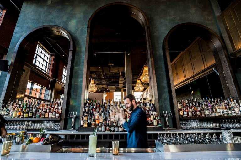 A bartender focused on mixing drinks, behind the bar of Death and Company. This bar lounge is located inside The Ramble Hotel.