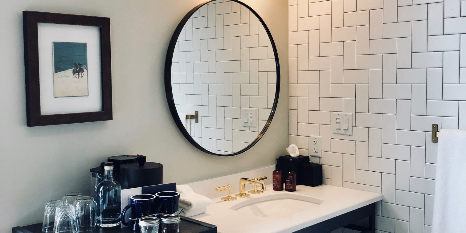 Close-up of the bathroom of The Bunkhouse inside The Ramble Hotel. A tiled wall meets a wall with a large round mirror on it. Beside the sink, complementary items rest on the mini-fridge.