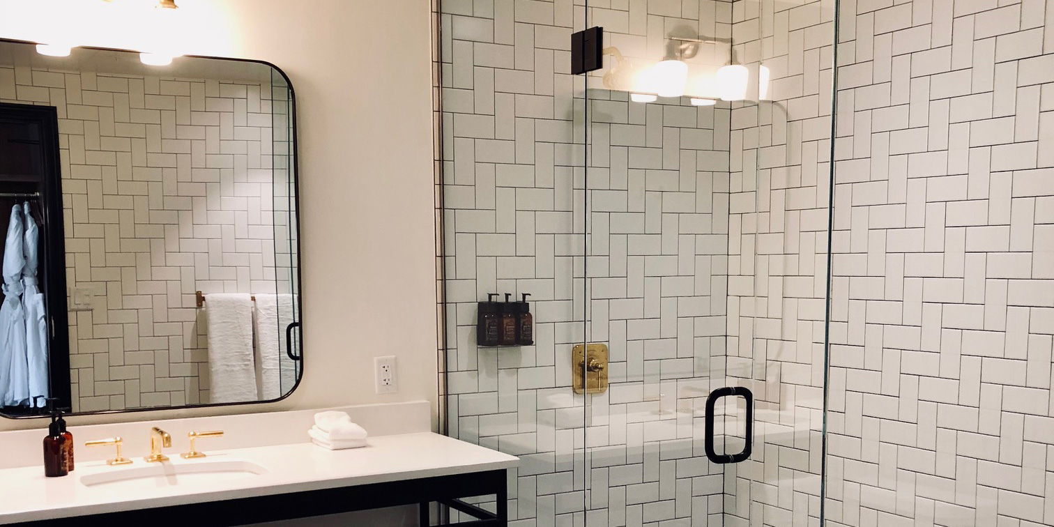 Perspective shot for Double Queen bathroom of The Ramble Hotel. A full length shower room is tucked in the corner.
