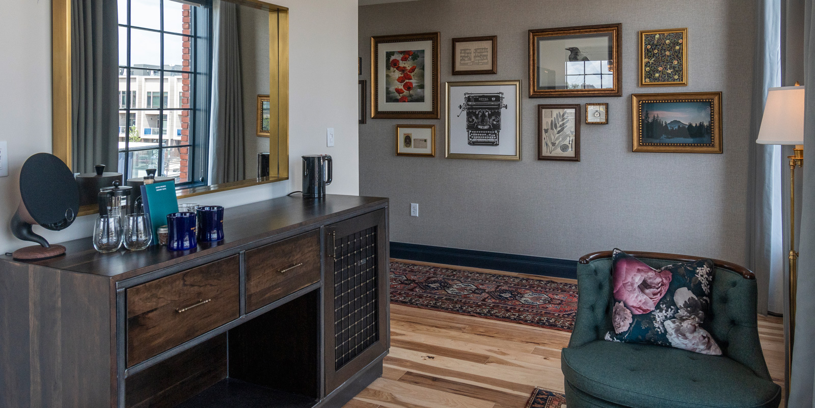 Wet bar of the Salon Suite inside The Ramble Hotel. Choose your favorite drink to serve up for guests. The art decorated hallway takes you to the bedroom and bathroom areas.