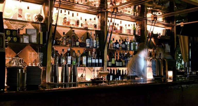 Action shot of a bartender moving and working behind the Death and Co. bar. Located inside The Ramble Hotel, the bartender is blurry as they were caught in action.