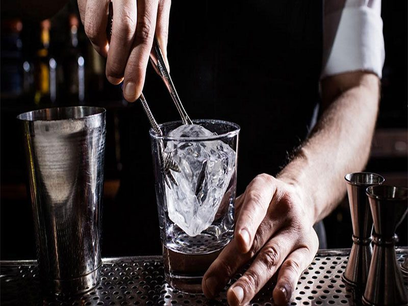 Closeup of a Death and Co. bartender placing a large ice cube into a glass.