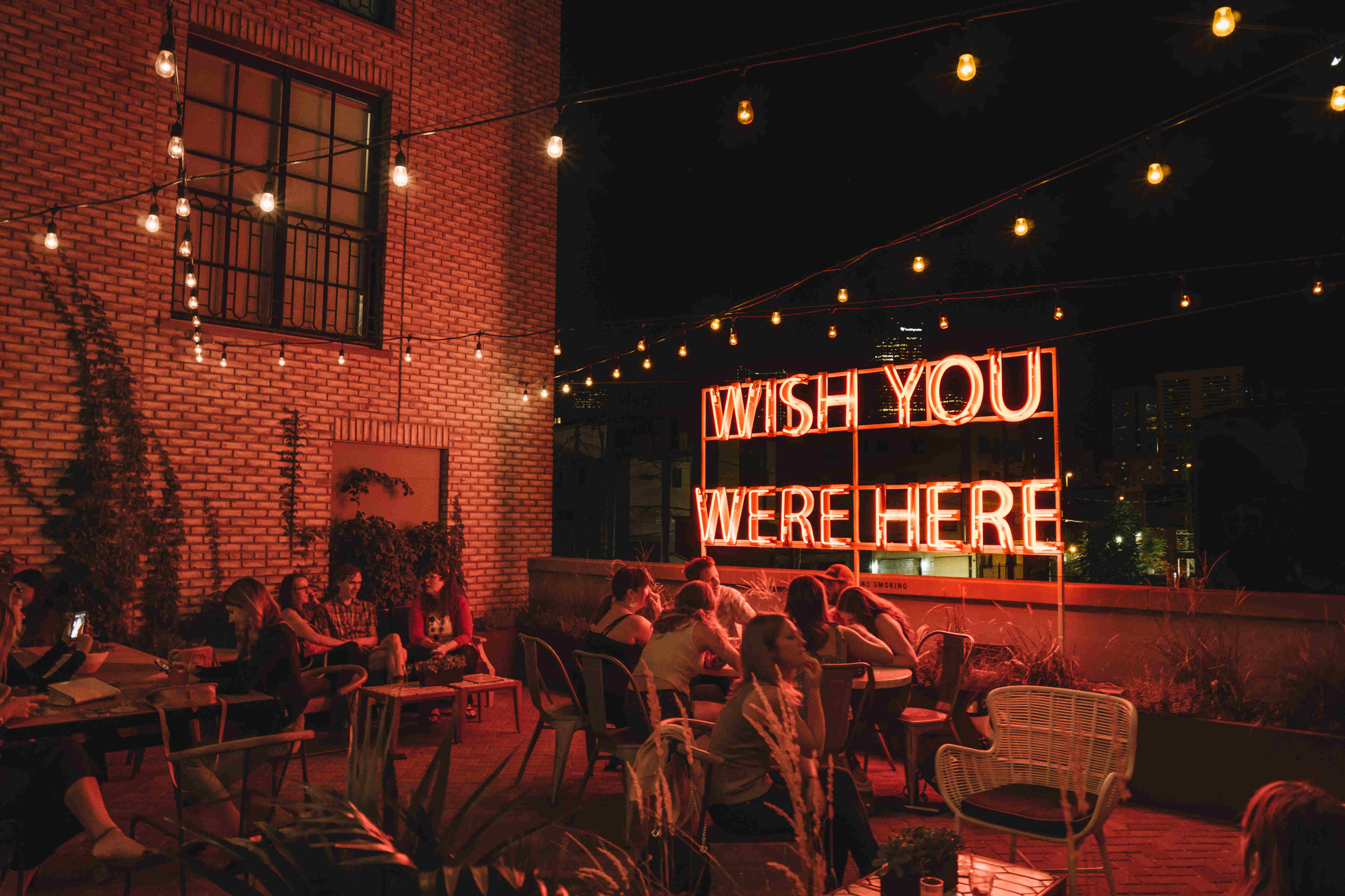 Perspective Shot for the Garden Terrace in the Ramble Hotel. The bar is full of people and there is a red shining billboard showing the message 'Wish you were here'