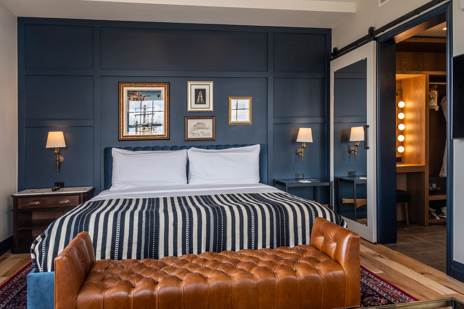 View of the king sized bed inside the Juliette King of The Ramble Hotel. A sliding door leads to the vanity and closet area.